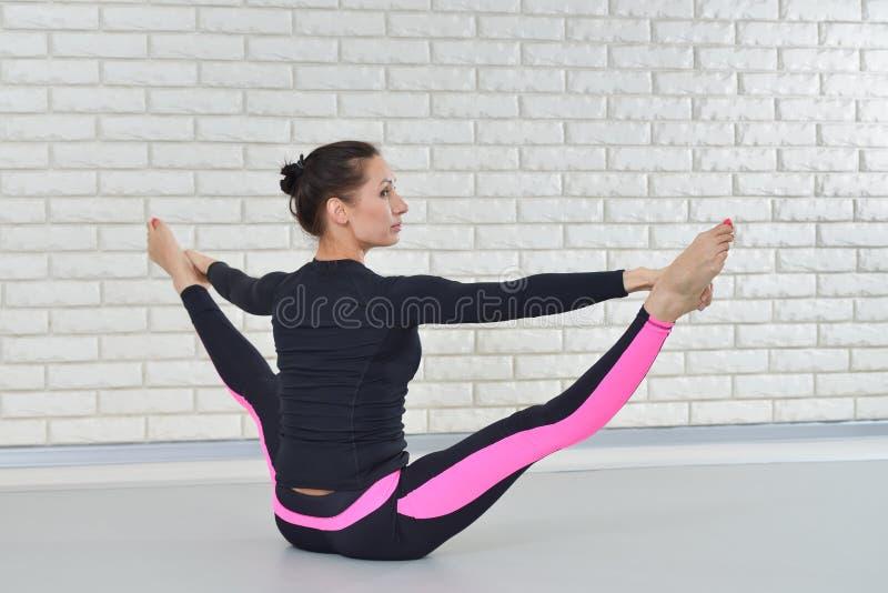 Schönheit in der Sportkleidung trainierend am Eignungsstudio, die Schnur durchführend, die auf dem Boden sitzt stockfoto