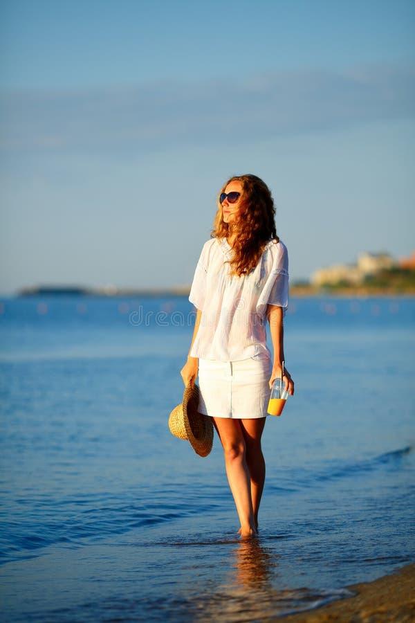 Schönheit in der weißen Kleidung mit Orangensaft, Sonnenbrille und Hut in der Hand auf dem Strand lizenzfreie stockfotografie