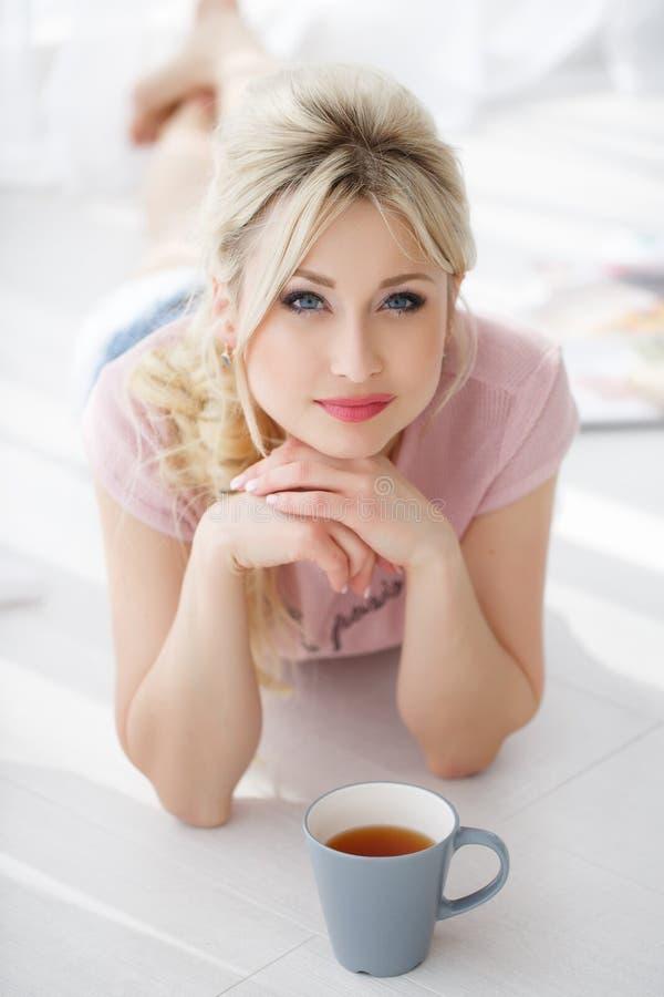 Schönheit, die auf einem weißen Boden mit einer Tasse Tee liegt lizenzfreie stockfotos