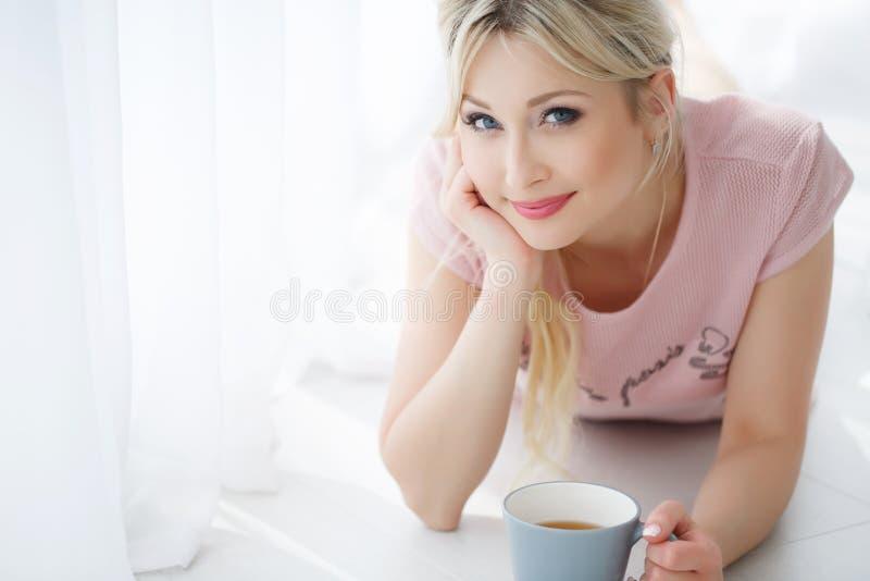 Schönheit, die auf einem weißen Boden mit einer Tasse Tee liegt stockfoto