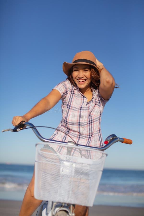 Schönheit, die auf Fahrrad am Strand im Sonnenschein sitzt lizenzfreies stockfoto