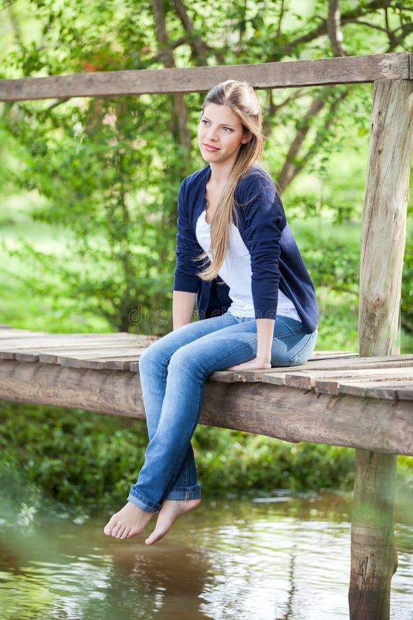 Schönheit, die auf Holzbrücke sitzt stockfoto