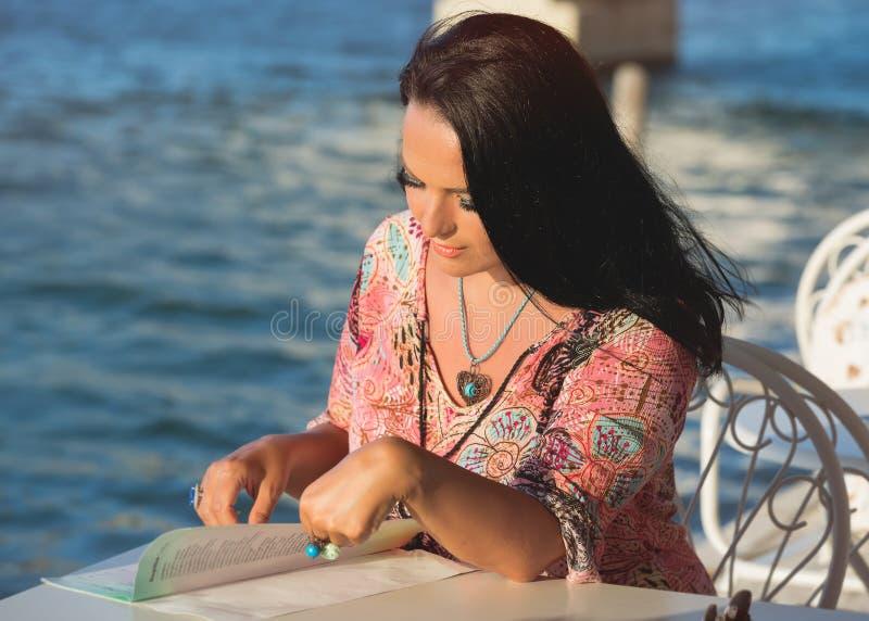 Schönheit, die das Menü an einem griechischen Küstenrestaurant liest lizenzfreie stockbilder