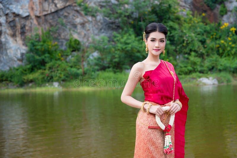 Schönheit, die das thailändische Trachtenkleid hält thailändische Artblume trägt lizenzfreie stockfotografie
