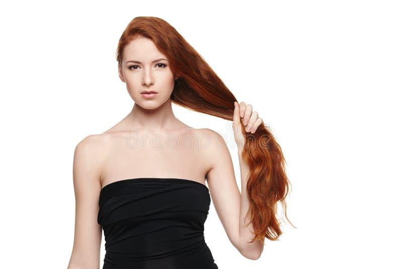 Schönheit, die in der Hand ihr rotes Haar hält stockbild