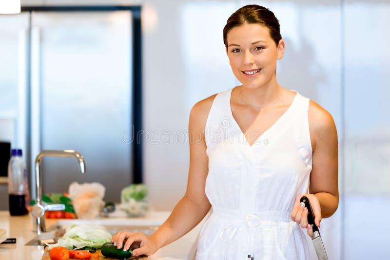 Schönheit, die in der Küche und im Lächeln steht stockbilder