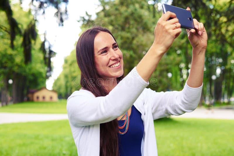 Schönheit, die an der Kamera lächelt, um ein selfie im p zu machen stockfotografie