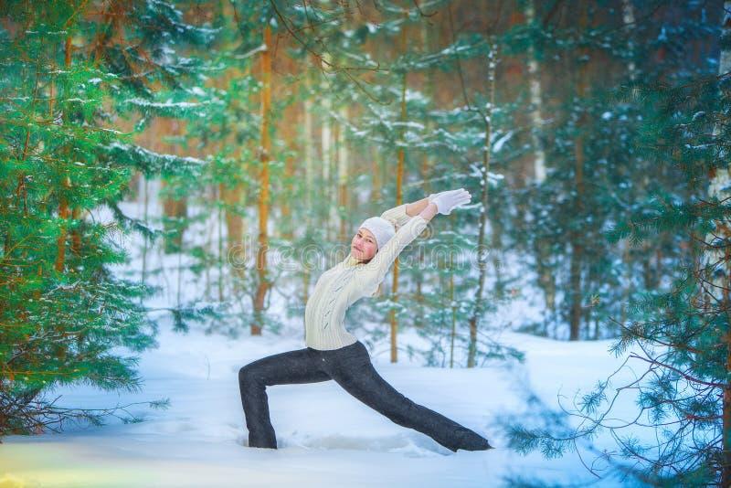 Schönheit, die draußen Yoga im Schnee tut stockbilder