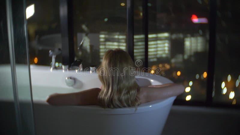 Schönheit, die ein entspannendes Bad in einem luxuriösen Badezimmer mit einem Fenster nachts genießt Das Konzept einer Lebensart stockfotos