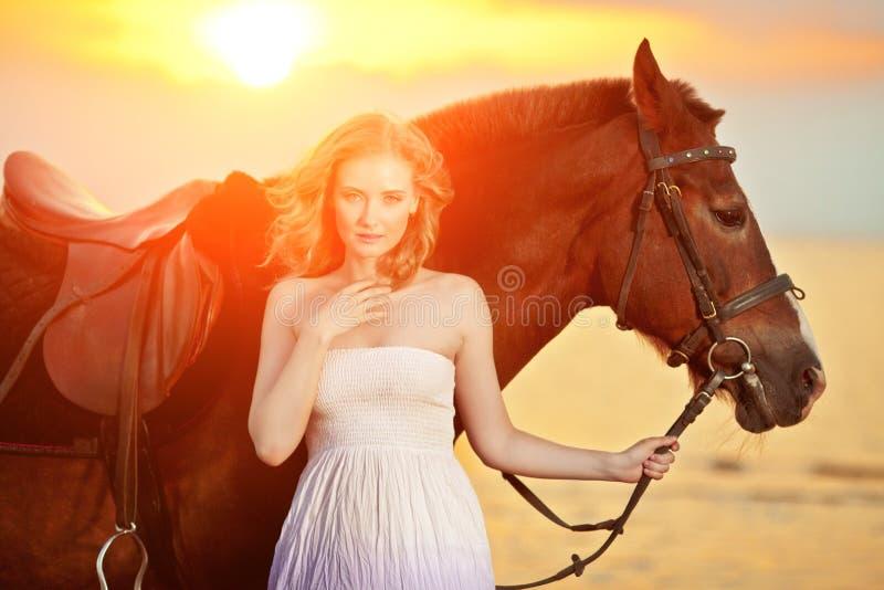 Schönheit, die ein Pferd bei Sonnenuntergang auf den Strand reitet Junges gir lizenzfreie stockbilder
