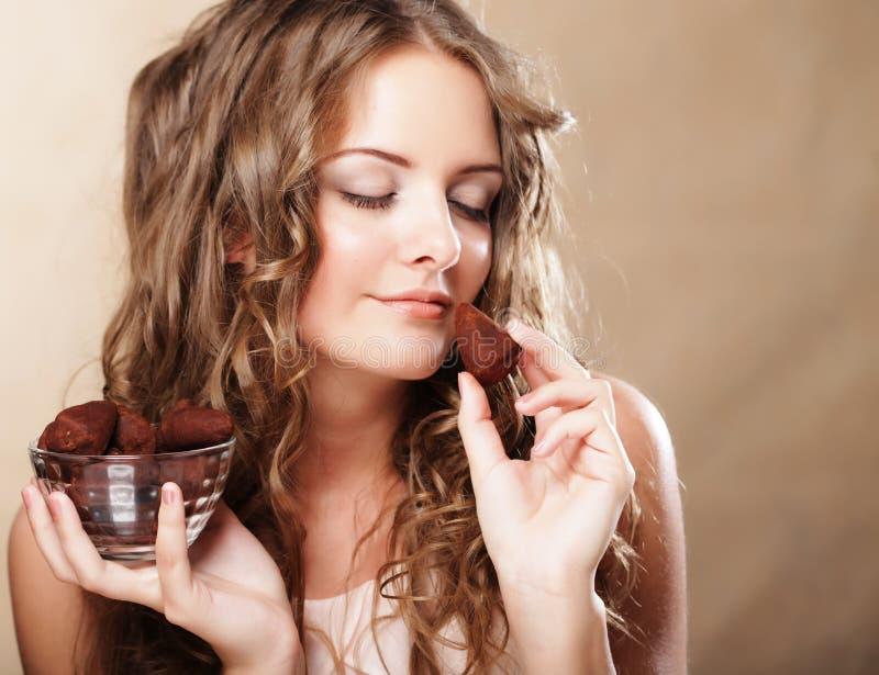 Schönheit, die ein Schokoladenbonbon isst lizenzfreie stockfotos