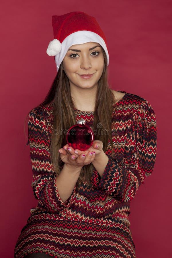 Schönheit, die eine Weihnachtsverzierung hält stockfotografie
