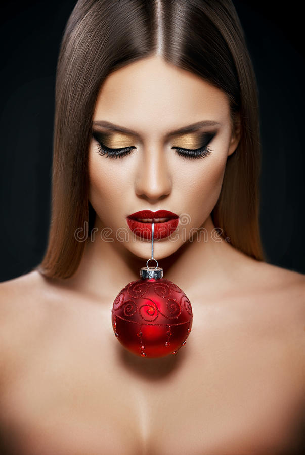 Schönheit, die eine Weihnachtsverzierung mit den Zähnen über dunklem Hintergrund hält stockbild