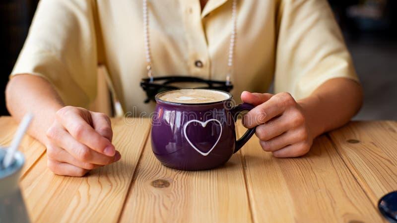 Schönheit, die in einem Café mit einem Tasse Kaffee sitzt Attraktive junge Frau trinkt Kaffee oder Cappuccino stockfoto