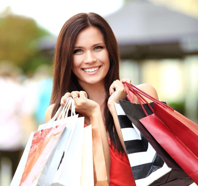 Schönheit, die Einkaufstaschen hält stockfoto