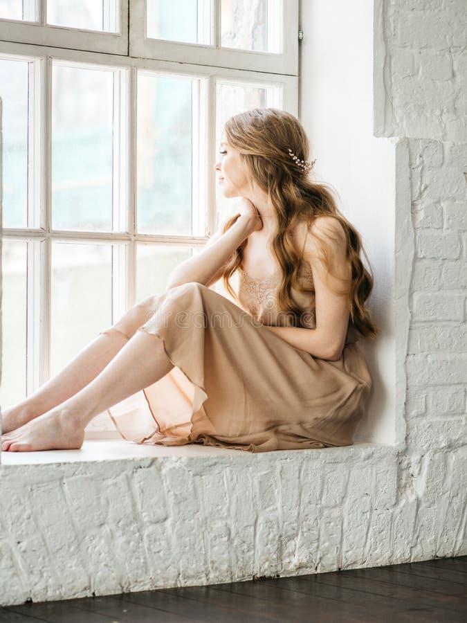 Schönheit, die am Fenster sitzt und extern schaut lizenzfreie stockfotos