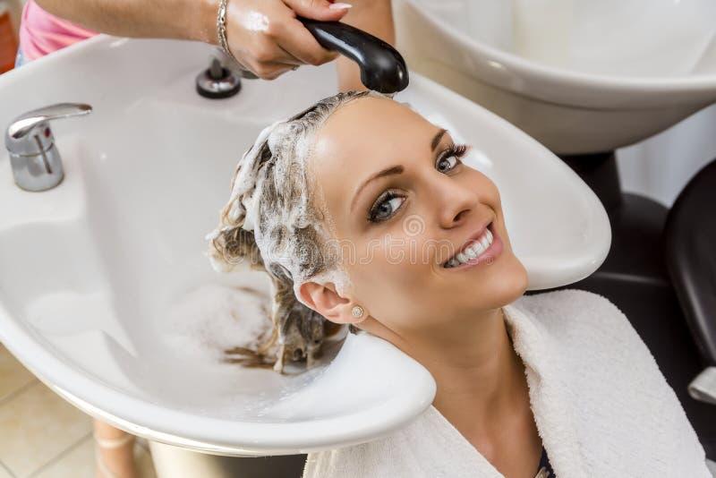 Schönheit, die Haarwäsche in einem Friseursalon erhält stockbild