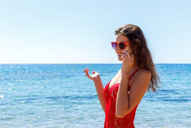 Schönheit, die am Handy auf dem Meer spricht lizenzfreie stockfotos