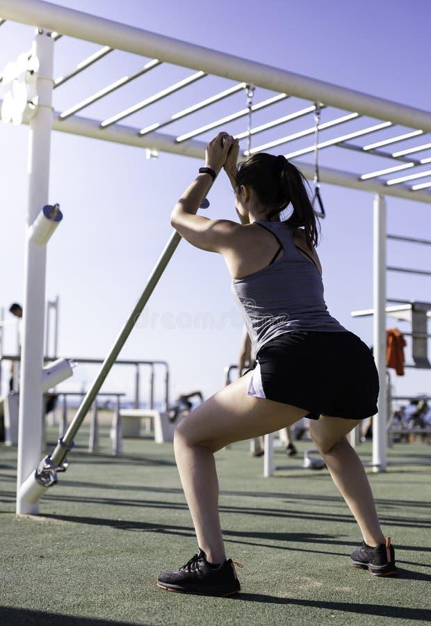 Schönheit, die Hocken mit Gewichtsbar Ausbildungsstellen- oder Straßentraining am im Freien in Barcelona-Strand u. in x28 tut; SP stockfoto
