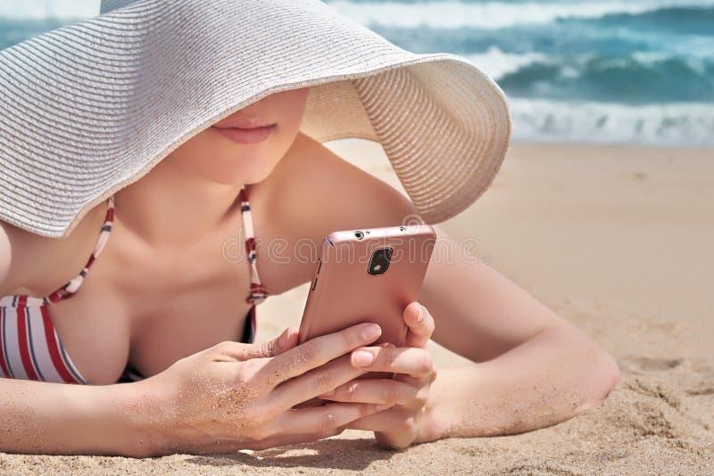 Schönheit, die ihre Smartphonedaten bei der Entspannung auf Strand verwendet stockbilder