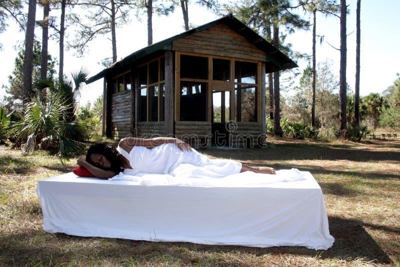 Schönheit, die in ihrem Bett im Freien schläft stockfotos