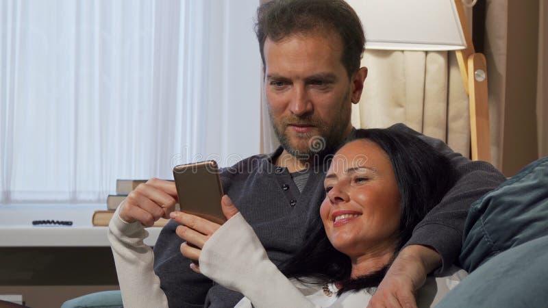 Schönheit, die ihrem Ehemann etwas lustig an ihrem intelligenten Telefon zeigt stockbild