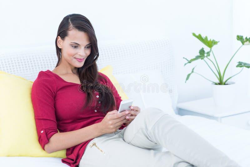 Schönheit, die ihren Smartphone sitzt auf Bett verwendet stockfotos