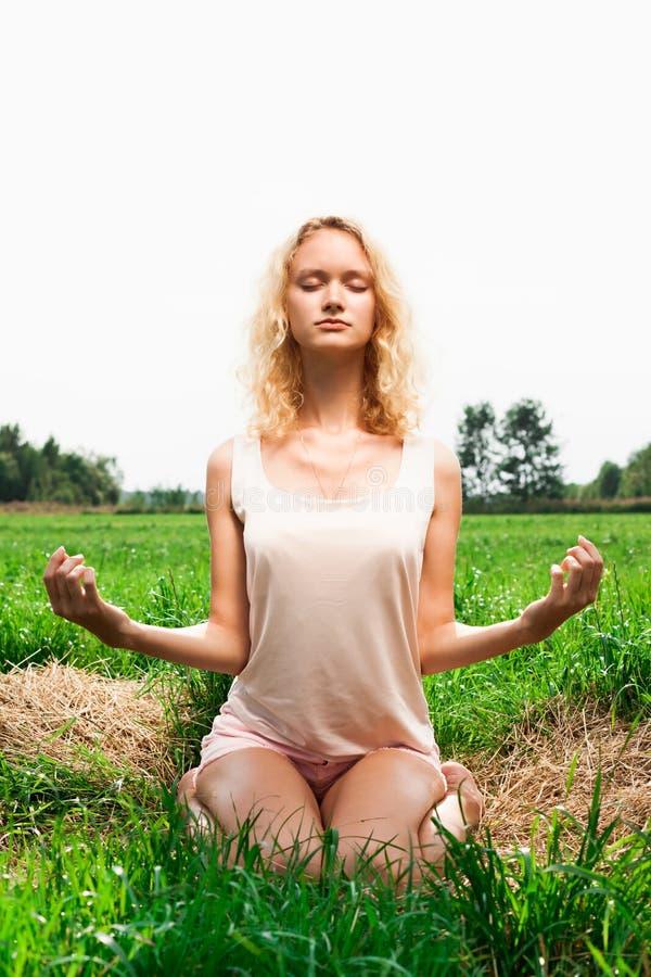 Schönheit, die im Sommerpark meditiert stockfotos