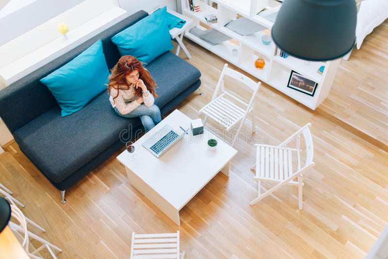 Schönheit, die im Wohnzimmer arbeitet stockbilder