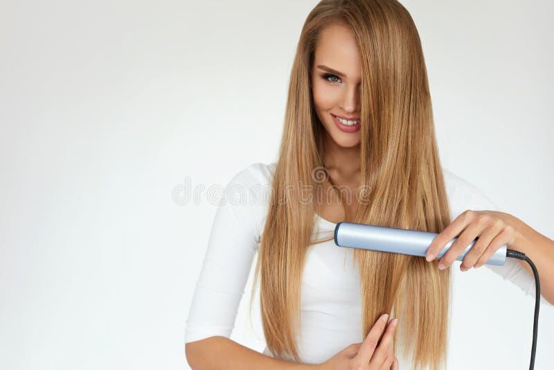 Schönheit, die langes gerades Haar mit Strecker bügelt stockbilder