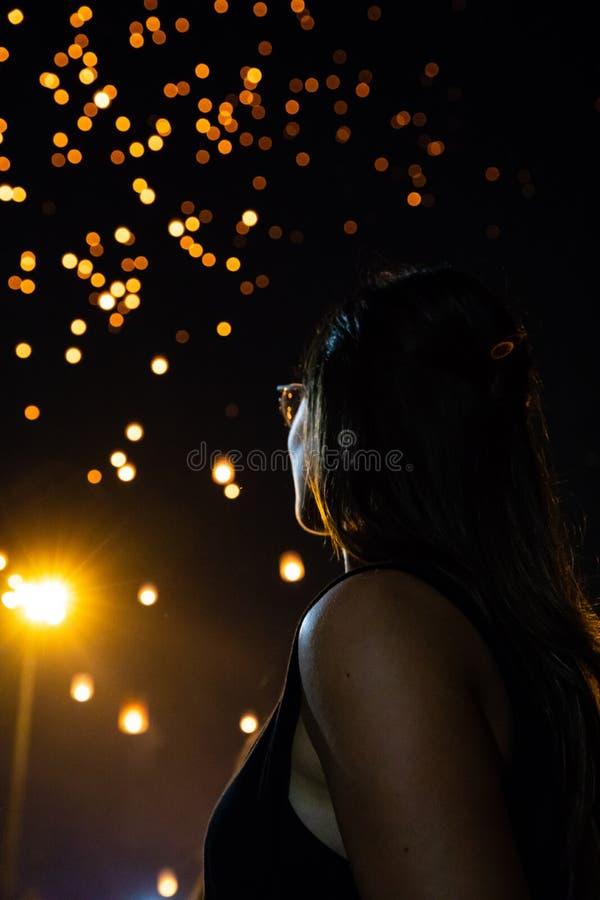 Schönheit, die Loy Krathong-Papierlaternen als bokeh auf Hintergrund in Thailand betrachtet lizenzfreies stockfoto