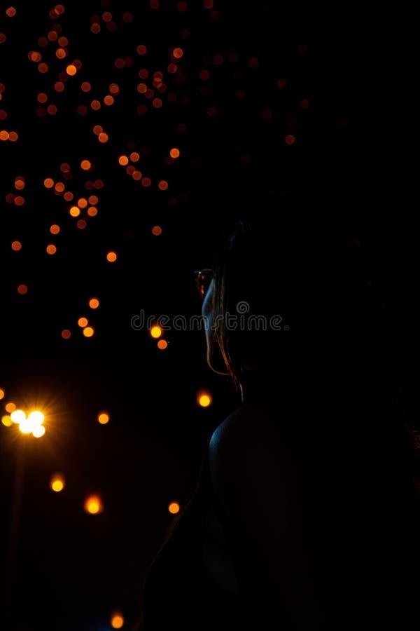 Schönheit, die Loy Krathong-Papierlaternen als bokeh auf Hintergrund in Thailand betrachtet lizenzfreies stockbild