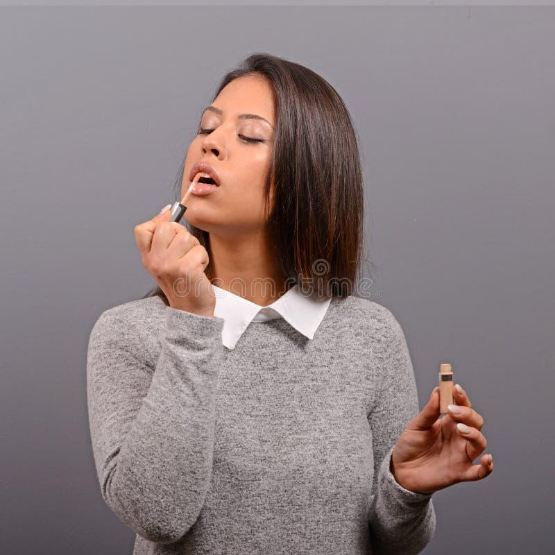 Schönheit, die Make-up auf Gesicht mit Lippenstift tut Mode-Modell, das gegen grauen Hintergrund aufwirft stockfotografie
