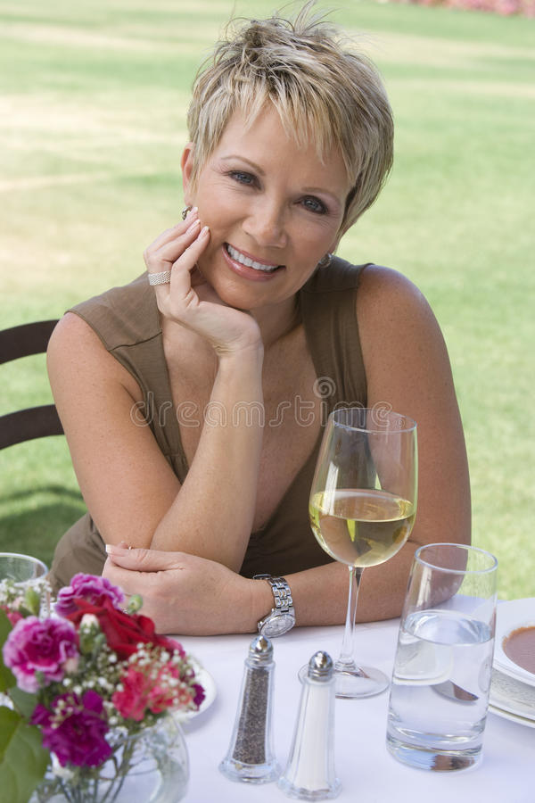 Schönheit, die mit einem Glas Wein sitzt stockbild