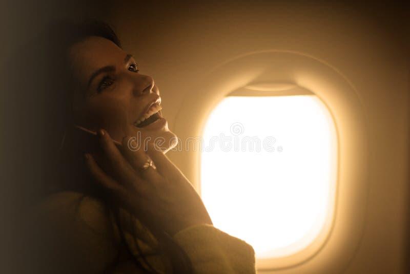 Schönheit, die mit Flugzeug reist Unterhaltung auf Handy lizenzfreies stockfoto