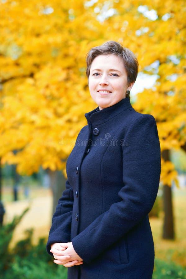 Schönheit, die mit gelben Blättern im Herbststadtpark, Herbstsaison aufwirft lizenzfreies stockbild