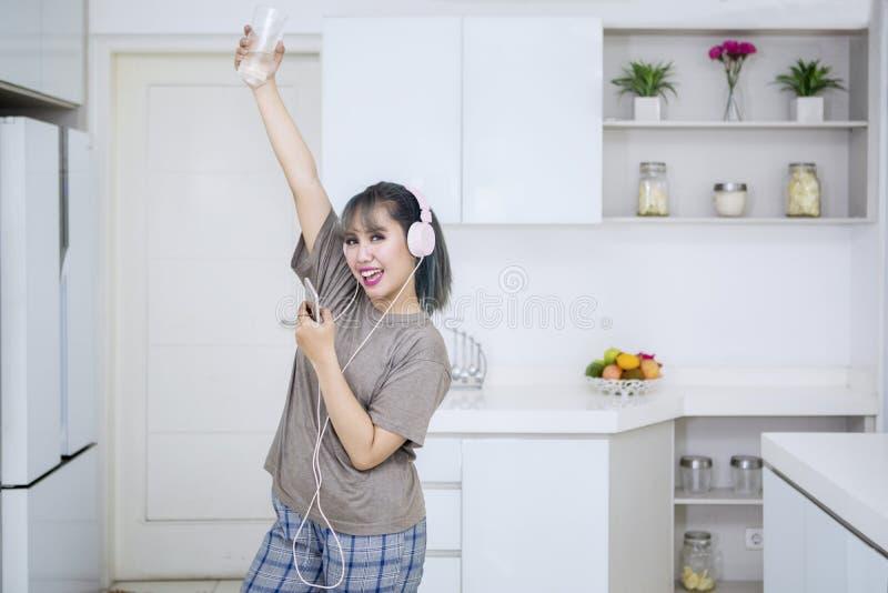Schönheit, die Musik in der Küche genießt stockfotos