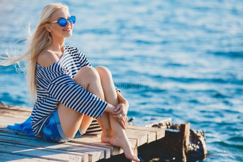 Schönheit, die nahe dem Meer sitzt lizenzfreies stockfoto