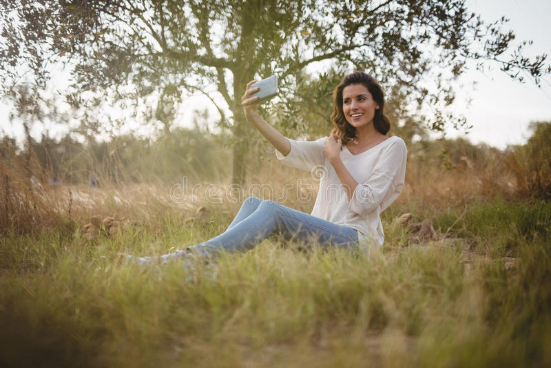 Schönheit, die selfie beim Sitzen auf grasartigem Feld nimmt lizenzfreie stockfotos