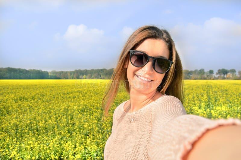 Schönheit, die selfie Foto von auf dem gelben Gebiet mit Naturhintergrund macht Schließen Sie herauf Portrait einer jungen Frau lizenzfreies stockfoto