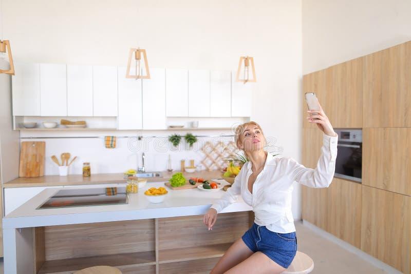 Schönheit, die selfie am Telefon auf Hintergrund von Küche t tut lizenzfreie stockfotografie