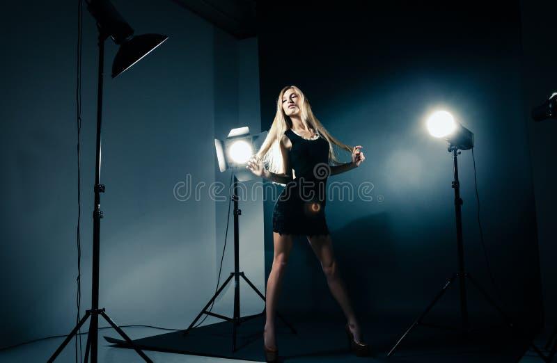 Schönheit, die am Studio in den hellen Blitzen aufwirft stockfotografie