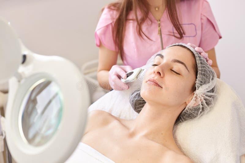 Schönheit, die Ultraschallgesichtsschale empfängt Reinigungsverfahren der Haut am Schönheitsbadekurortsalon Cosmetologist macht d stockbild