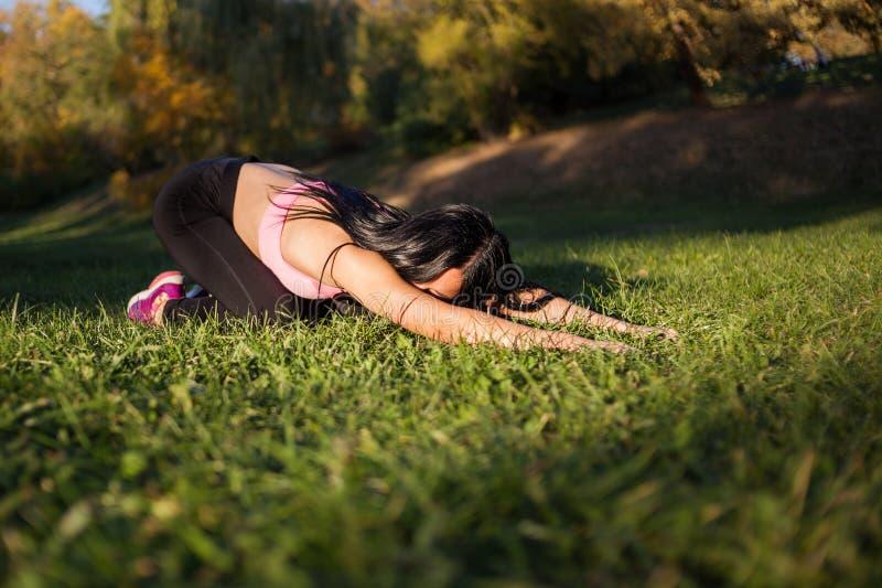 Schönheit, die Yoga in der Natur im Park - Reihe Gruß des sonnen- Balasana oder der Position eines Kindes tut Am Sonnenuntergang lizenzfreie stockbilder