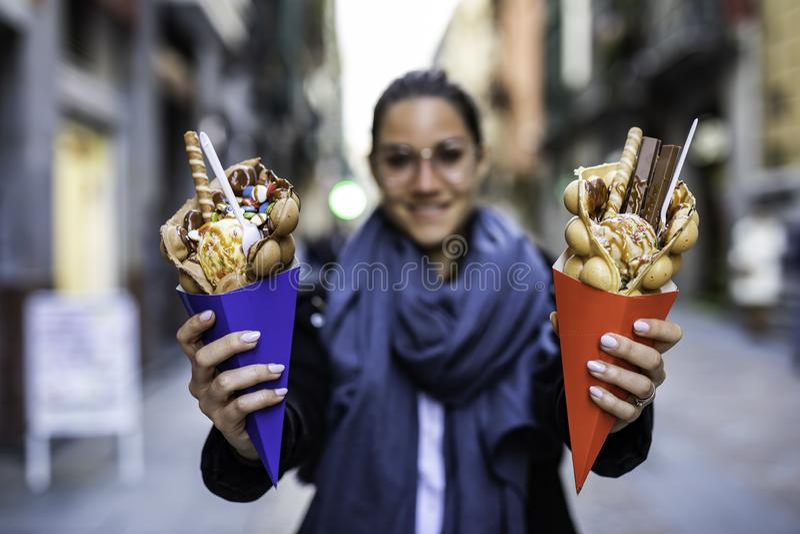 Schönheit, die zwei Blasenwaffeln mit Eiscreme und Süßigkeiten auf den blauen und roten Papierkegeln mit unscharfem unerkennbarem lizenzfreie stockbilder