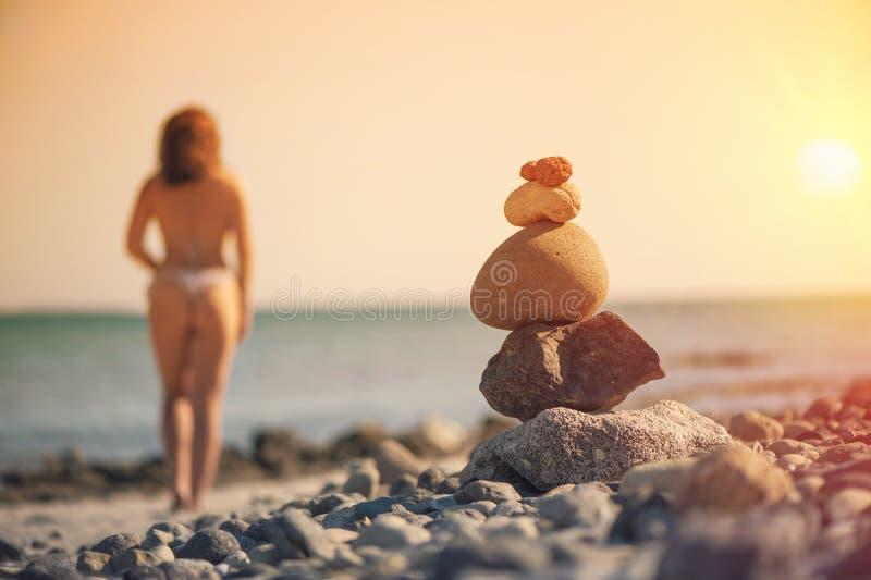 Schönheit in einem Badeanzug gehend entlang den Strand vor dem hintergrund einer Pyramide von Steinen Unscharfe Frau mit Steinen  lizenzfreies stockbild