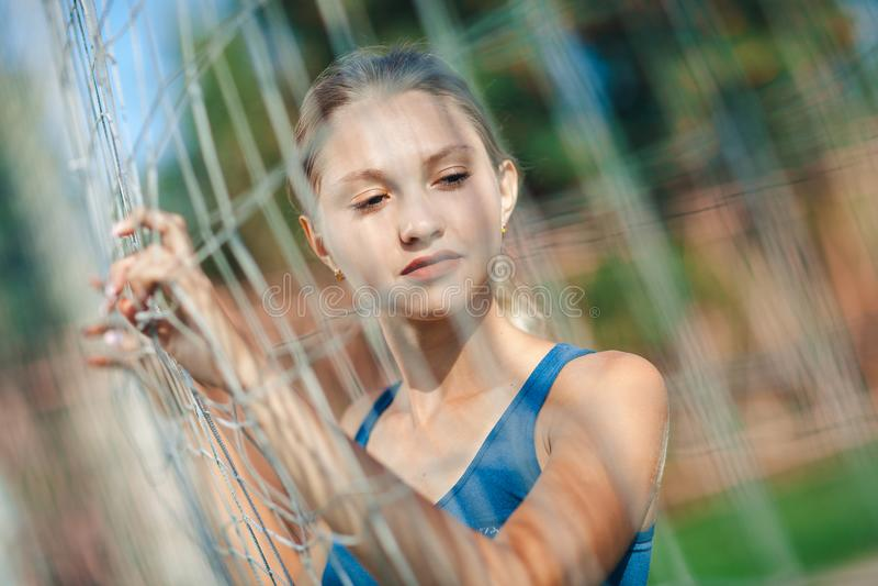 Schönheit in einem blauen Hemd und in Gamaschen, die auf einem Fußballplatz nahe dem Gitter stehen lizenzfreie stockbilder