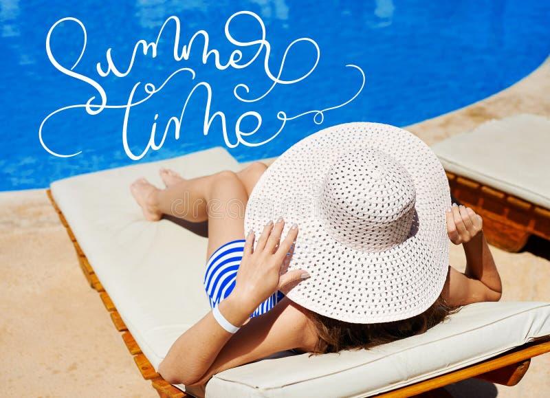 Schönheit in einem großen weißen Hut auf einem Ruhesessel bis zum der Pool und Text Sommerzeit Kalligraphiebeschriftungs-Handabge stockbilder