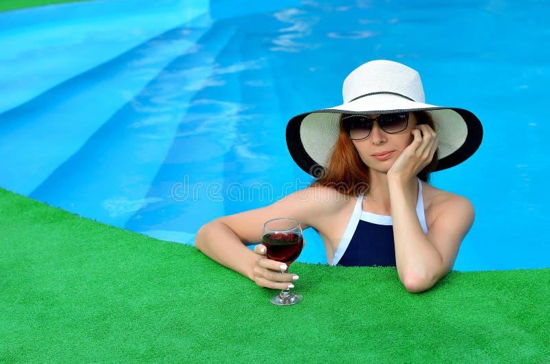Schönheit in einem Hut und in der Sonnenbrille im Pool lizenzfreie stockfotos