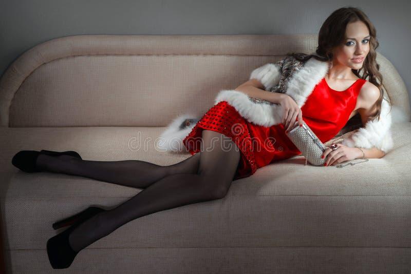 Schönheit in einem Kleid auf einem Sofa stockfotografie